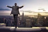 Imprenditore in piedi con le braccia aperte in cima a ny — Foto Stock