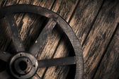 Old wheel on a wooden background — Stock Photo