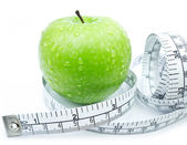 Green apple with measuring tape on white background — Stock Photo