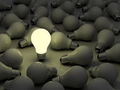 One glowing light bulb standing out from the unlit incandescent bulbs — Stock Photo