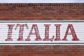 """Old Hand-Painted Sign """"Italia"""" on a Brick Wall — Stock Photo"""