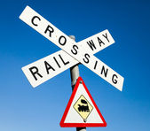 Railway crossing sign against a blue sky — Stock Photo