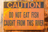 Old Rusted Sign Reading: Caution Do Not Eat Fish Caught from thi — Stock Photo
