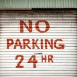 Sign on Lane Garage Door Stating NO PARKING 24 HR — Stock Photo #47846841