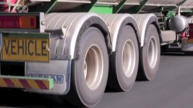 Close up of wheels of a semi trailer travelling at speed on the highway.