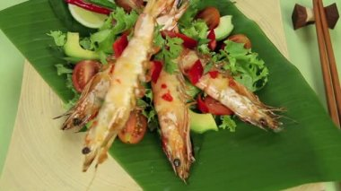 Putting skewered Asian shrimps onto a bed of garden salad. — Stock Video