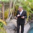 Mature businessman walking by a swimming pool to camera working with a tablet. — Stock Video #44590119
