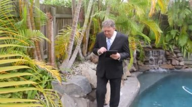 Mature businessman walking by a swimming pool to camera working with a tablet. — Stock Video