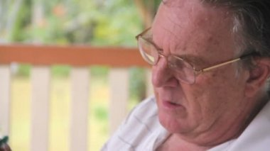 Mature man sitting and relaxing on his verandah playing sudoku. — Stock Video