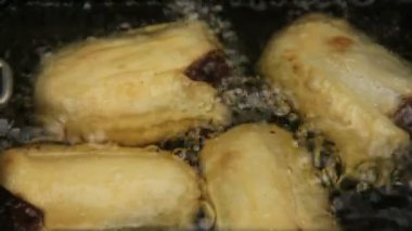 Basket of crisp golden dim sums cooking and bubbling in hot oil. — Stock Video