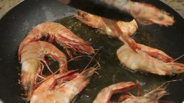 Whole shrimps being fried in a fry pan with oil being turned over with tongs. — Stock Video