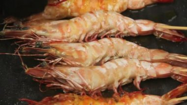 Single whole shrimps on skewers being turned in a griddle fry pan. — Stock Video