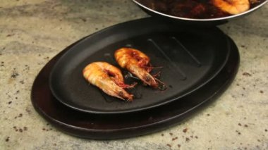 Fried shrimps being put in a baked hot iron pan and sizzling with asian marinade being poured over them. — Stock Video