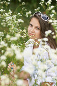 Girl sitting surrounded by daisies — Stock fotografie