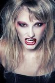The portrait of a blond girl vampire — Stock Photo