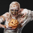 Scary mummy waves her arms with pumpkin — Stock Photo #13851594