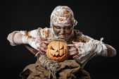 Scary mummy holding the pumpkin — Stock Photo