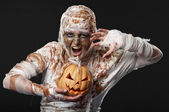 Scary mummy waves her arms with pumpkin — Stock Photo