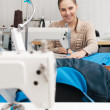 Young smilling seamstress at work — Stock Photo