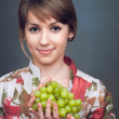 The girl is holding fresh grapes — Stock Photo