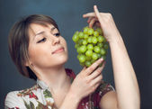 The girl is looking on grapes — Stock Photo