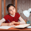 Thoughtful girl doing homework at the table — Stock Photo #22330443