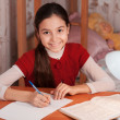 Girl doing homework in a notebook — Stock Photo