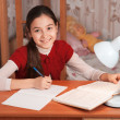 Girl doing homework in a notebook — Stock Photo #22330553