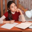 Thoughtful girl doing homework at the table — Stock Photo #22330559