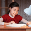 Girl at desk reading a book by light of the lamp — Stock Photo