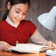 Girl at desk reading a book by light of the lamp — Stock Photo #22330627