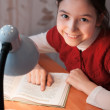 Girl at desk reading a book by light of the lamp — Stock Photo #22330665