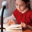 Girl at desk reading a book by light of the lamp — Stock Photo #22330715