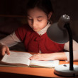 Stock Photo: Girl at desk reading a book by light of the lamp