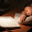 Girl asleep at a table doing homework — Stock Photo