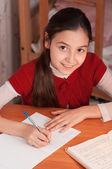 Chica haciendo los deberes en un cuaderno — Foto de Stock