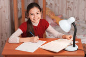 Girl doing homework in a notebook — Stok fotoğraf