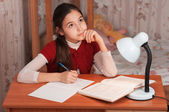 Thoughtful girl doing homework at the table — Stock Photo