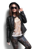 Girl in a leather jacket and black hat — Stock Photo
