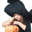 Little witch considers collected candy — Stock Photo #32393957