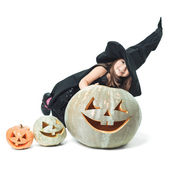 little witch hiding behind pumpkins — Stock Photo
