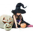 Little witch sits near tykov and considers candies — Stock Photo