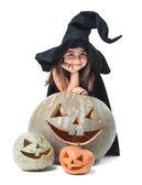 Little witch hiding behind pumpkins — Stock Photo