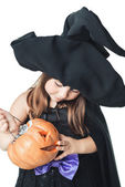 Little witch considers collected candy — Stock Photo