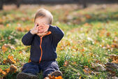 Boy sitting on the grass and hides — Stock Photo