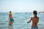 Boy and girl playing frisbee in the water — Stock Photo