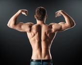 Bodybuilder showing muscles back and arms — Fotografia Stock