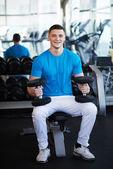 Bir dumbbell ile bankta oturan genç spor adamı — Stok fotoğraf