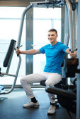 Man exercising in trainer for pectoral muscles — Stock Photo