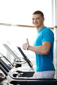 Man showing thumbs up near the treadmill — Stock Photo